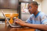 child on laptop at kitchen table