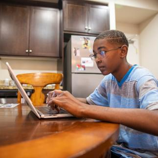 child on laptop at kitchen table